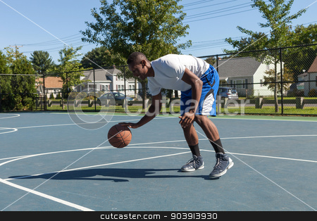 Basketball Player Dribbling stock photo, A sweaty young basketball player dribbling down the court demonstrating his ball handling skills. by Todd Arena