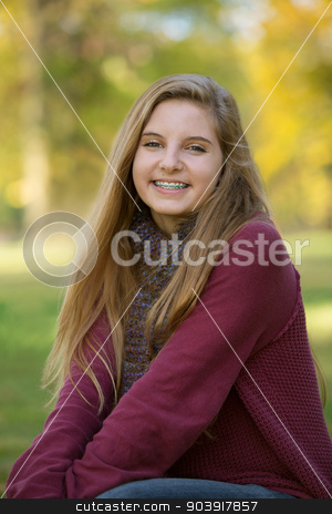 Cute Teen in Red Sweater stock photo, Beautiful teenage girl in red sweater sitting outdoors by Scott Griessel