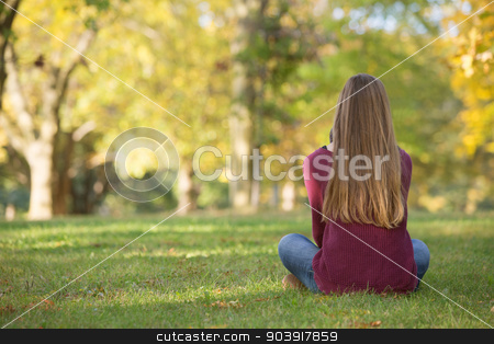 Rear View of Sitting Girl stock photo, Unidentifiable woman sitting cross legged on grass by Scott Griessel