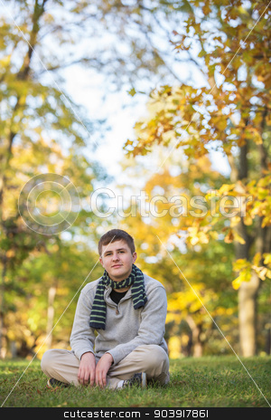 Calm Teen in Autumn stock photo, Calm Caucasian teenager sitting on grass during the  autumn season by Scott Griessel