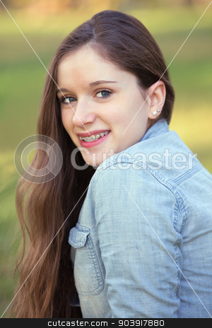 Pretty Girl Looking Over stock photo, Pretty teenage girl smiling and looking over her shoulder by Scott Griessel