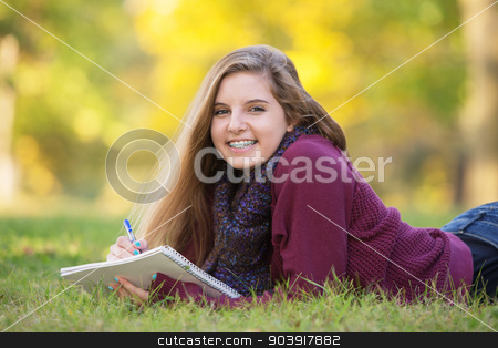 Female Teen on Ground Studying stock photo, Female teen with braces taking notes while laying on ground by Scott Griessel