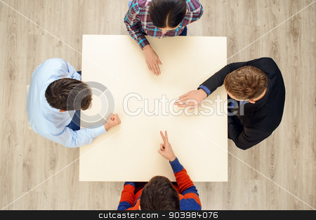 Top view people playing rock paper scissors stock photo, Top view of table with group of creative people playing rock paper scissors game by Dmytro Sidelnikov