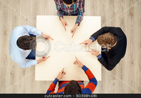 Top view table with pointing at each other people stock photo, Top view of table with group of creative people working on project. Everyone of team pointing at each other by Dmytro Sidelnikov
