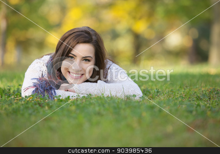 Happy Teen Laying On Grass stock photo, Happy smiling young woman laying down on grass by Scott Griessel