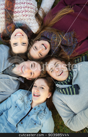 Five Teens Close Together stock photo, Group of five Caucasian teenagers laying down on grass together by Scott Griessel
