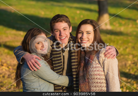 Handsome Teen Boy with Girls stock photo, Smiling handsome teen male with happy girlfriends outdoors by Scott Griessel