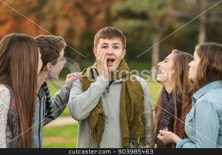 Surprised Male Teen with Friends stock photo, Surprised male teenager with laughing group of friends by Scott Griessel
