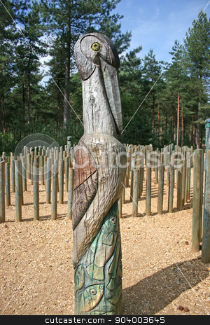 Totem Pole stock photo, A totem pole with a bird and fishes in the forest by Lucy Clark