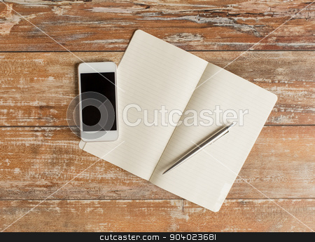 close up of notebook, pen and smartphone stock photo, business, education, objects and technology concept - close up of notebook, pen and smartphone on table by Syda Productions