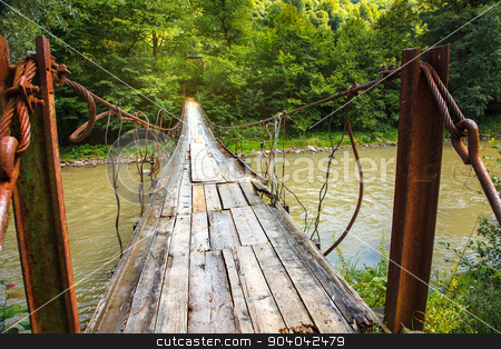 Bridge in the forest stock photo, Suspension bridge across mountain river by serkucher