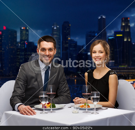 smiling couple eating main course at restaurant stock photo, people, celebration, romantic and holidays concept - smiling couple eating main course with red wine at restaurant over night city background by Syda Productions