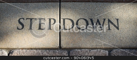 Step Down stock photo, Stone step Down sign on the ground. by Henrik Lehnerer