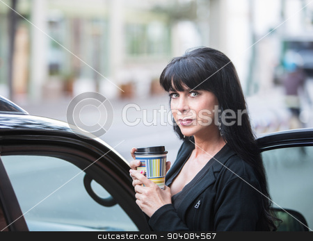 Beautiful Woman Downtown with Coffee stock photo, Attractive woman downtown in the morning with coffee cup by Scott Griessel