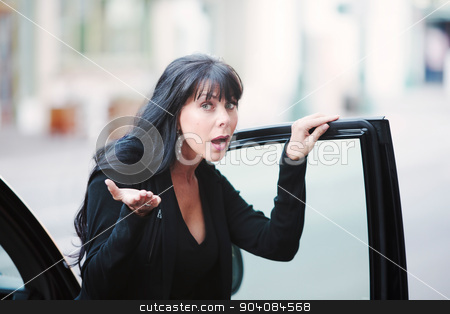 Skeptical Woman stock photo, Skeptical mature woman near car in urban environment by Scott Griessel