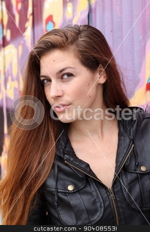 Portrait of a young woman stock photo, Portrait of a young woman in front of a colorful wall. by Henrik Lehnerer