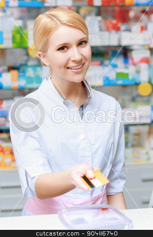Pharmacist working at the drugstore stock photo, Make purchase with the credit card. Young smiling blond pharmacist stretching out a credit card looking at the camera by Viacheslav Iakobchuk