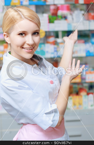 Pharmacist working at the drugstore stock photo, Big choice of medicines. Female smiling pharmacist presenting blurred range of medication on the background by Viacheslav Iakobchuk