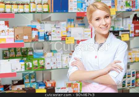 Range of medicine in the drugstore stock photo, Everything for the best therapy. Young smiling druggist in white uniform standing with her arms crossed near the show case of a drug store by Viacheslav Iakobchuk