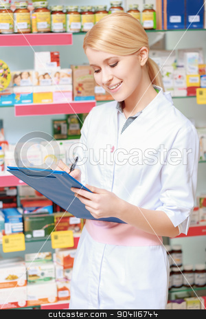 Druggist makes notes in a clipboard stock photo, Monitor availability of medicine. Portrait of blonde pharmacist or health care worker with clipboard standing in a drugstore by Viacheslav Iakobchuk