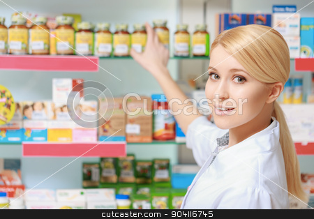Chemist points to the show case stock photo, Follow the prescription. Young blonde pharmacist picking medicine and drugs from shelves in the drugstore by Viacheslav Iakobchuk