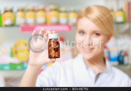 Druggist holds a blister of pills stock photo, Placebo. Close-up of a bottle with pills in selective focus which holds a female therapist standing by the shelves in drugstore by Viacheslav Iakobchuk