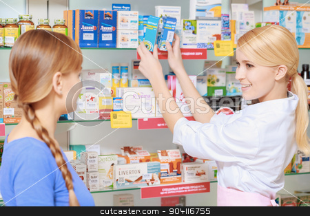Pharmacist and a customer choosing medicine stock photo, Quick and effective treatment. Young blonde druggist picks medicines from the shelf and talks to the female customer by Viacheslav Iakobchuk