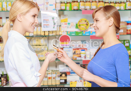 Making purchase in a drugstore stock photo, Payment with a card. Young smiling customer stretching out a credit card to the nice-looking pharmacist at the pharmacy counter by Viacheslav Iakobchuk