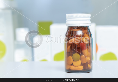 Medicines in a drug store stock photo, Power of medicine. Close-up of a glass bottle with multicolored pills inside by Viacheslav Iakobchuk