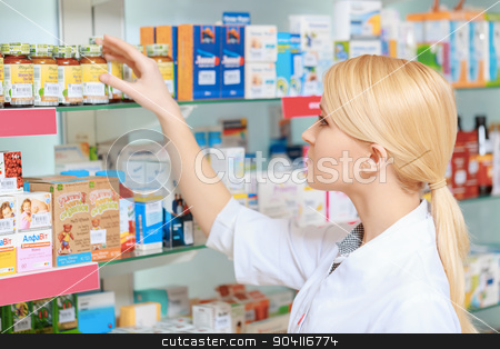 Pharmacist arranging medicines on the shelves stock photo, Searching for a right medicine. Portrait of beautiful blonde female pharmacist reading a label of the medicines in drug store by Viacheslav Iakobchuk