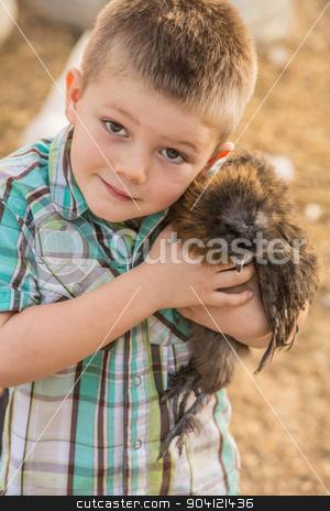 Boy Hugging Pet Chicken stock photo, Smiling boy outside hugs his pet chicken by Scott Griessel