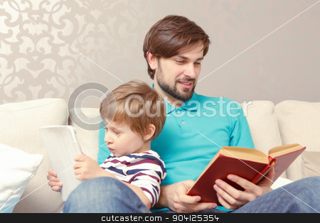 Father and son read a book or tablet stock photo, Different generations. Young father reading a book while his lovely son using a tablet device sitting at the home couch by Zinkevych