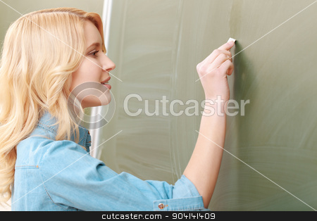 Student writes on a chalkboard stock photo, Decent student. Close-up of a beautiful young female student writing with a chalk on a blackboard by Zinkevych