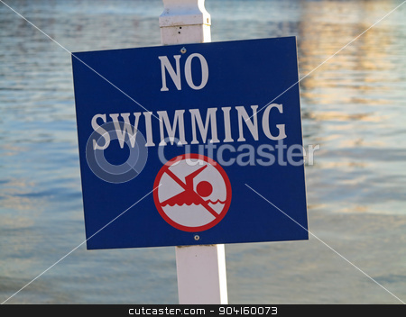 No Swimming Sign stock photo, A sign showing no swimming in the water behind by Lucy Clark