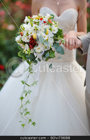 Bride holding wedding bouquet of colorful flowers and roses  stock photo, Bride holding wedding bouquet of colorful flowers and roses  by timonko