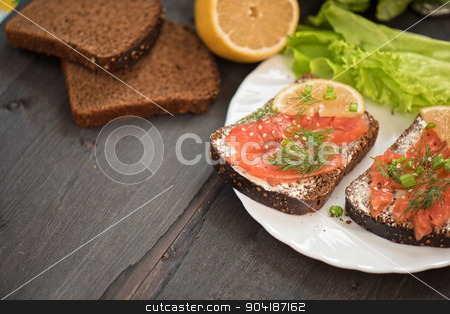 Sandwich with salmon for breakfast stock photo, Homemade sandwich with salmon and rye bread , butter lemon, and lettuce for breakfast by olinchuk