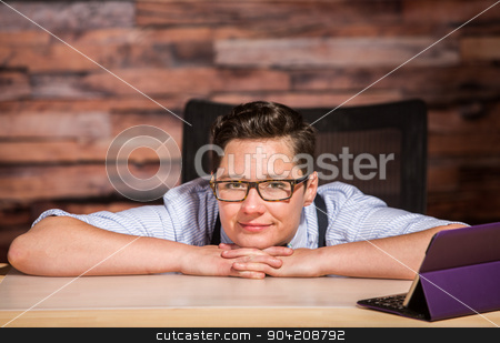 Dapper Woman in Bowtie with Tablet stock photo, Dapper woman in glasses sitting at modern desk with a tablet by Scott Griessel