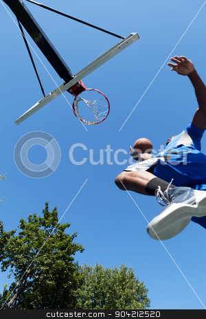 Basketball Dunk from Below stock photo, Young basketball player driving to the hoop for a high flying slam dunk. Shallow depth of field. by Todd Arena