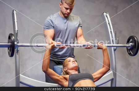 man and woman with barbell flexing muscles in gym stock photo, sport, fitness, teamwork, bodybuilding and people concept - young woman and personal trainer with barbell flexing muscles in gym by Syda Productions