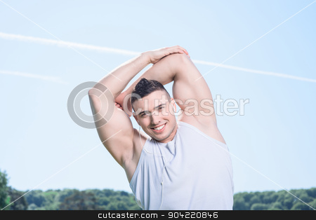 Portrait of a handsome sportsman  stock photo, Portrait of a young handsome sportsman making light exercises in the park on sunny day holding his arms behind his head, wearing white short and smiling   by Viacheslav Iakobchuk