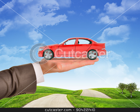 Car on businessmans hand stock photo, Car on businessmans right hand on blue sky background and green grass by cherezoff