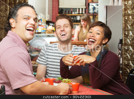 Laughing Group in Cafe stock photo, Laughing group of young adults sitting in cafe by Scott Griessel