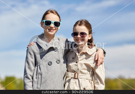 happy little girls in sunglasses hugging outdoors stock photo, people, children, friends and friendship concept - happy little girls in sunglasses hugging outdoors by Syda Productions