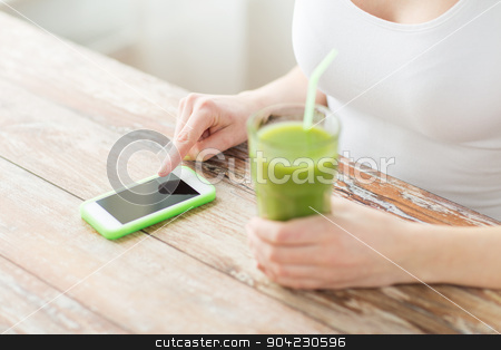 close up of woman with smartphone and green juice stock photo, healthy eating, diet, detox, technology and people concept - close up of woman with smartphone and green juice sitting at wooden table by Syda Productions