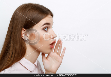 Beautiful girl showing emotions stock photo, Portrait of a young beautiful girl with long brown hair wearing pink cotton blouse, standing in a profile telling someone a secret holding her hand near mouth, on a white background by Zinkevych