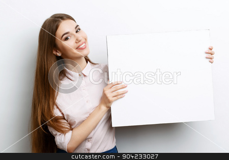 Beautiful girl with copy space stock photo, Portrait of a young beautiful girl with long brown hair wearing pink cotton blouse, standing waist up smiling and holding a copy space in her hands charming , on a white background by Zinkevych