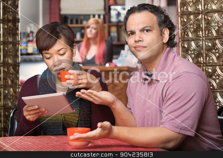 Spouse Reading Tablet and Annoying Husband stock photo, Annoyed spouse sitting with wife reading tablet computer by Scott Griessel