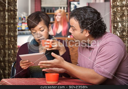 Woman on Tablet Ignoring Man stock photo, Woman distracted with tablet while man tries talking to her by Scott Griessel