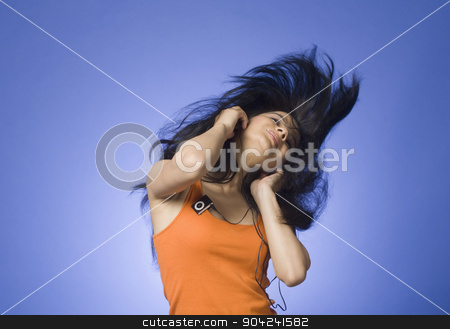 pims_20090226_sh0588.jpg stock photo, Young woman listening an MP3 player against blue background by imagedb