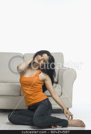 pims_20090226_sh0640.jpg stock photo, Young woman stretching near a couch by imagedb